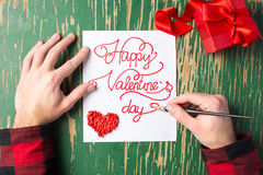 Male hands writing a Valentines day card. Male hands writing a calligraphy Valentines day card Stock Images