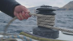 Male hands of yachtsman pull and reel up ropes on board sailing yacht close up
