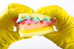 Male hands in yelliw gloves holding a burger made from sponges different colors. Concept of unhealthy food and non. Male hands holding a burger made from sponges royalty free stock images