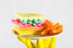 Male hands in yelliw gloves holding a burger made from sponges different colors. Concept of unhealthy food and non. Male hands holding a burger made from sponges stock photo