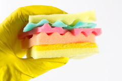 Male hands in yelliw gloves holding a burger made from sponges different colors. Concept of unhealthy food and non. Male hands holding a burger made from sponges royalty free stock photo