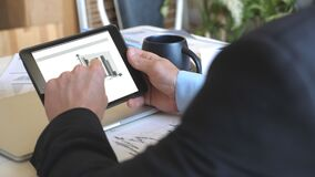 Male hands of young businessman developing a business project and analysing statistical data information on a tablet pc