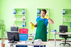 The male handsome professional cleaner working in the office. Male handsome professional cleaner working in the office Royalty Free Stock Image