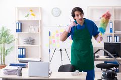 The male handsome professional cleaner working in the office. Male handsome professional cleaner working in the office royalty free stock photography
