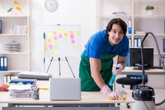 The male handsome professional cleaner working in the office. Male handsome professional cleaner working in the office stock photography
