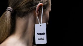 Male hanging good girl label on female ear, submission to man rules, disrespect. Stock footage stock video footage