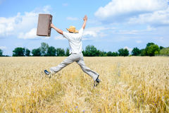 Male in hat jumping with retro suitcase on wheat. Picture of man in hat jumping with old suitcase on wheat field. Excited traveller on summer sunny countryside Royalty Free Stock Photos