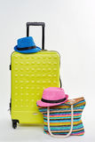 Male hat, wheeled suitcase. Male, wheeled suitcase. Bright handbag and hat of woman. Colorful accessories for summer vacation Stock Photography