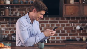 Male have breakfast and use smart phone at home. stock video footage