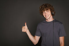 Male in headphones gesturing thumb up. Happy male in headphones gesturing thumb up, against gray background Stock Image