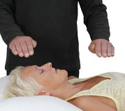 Male Healer and female client. Male healer with hands hovering above forehead and heart of female client Royalty Free Stock Photography