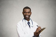 Male health care professional, doctor taking patient notes. Closeup portrait, confident, smiling young male family doctor, cardiologist, health care professional Stock Photo