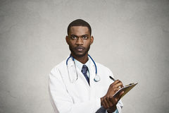 Male health care professional, doctor taking patient notes. Closeup portrait, confident young male family doctor, assistant cardiologist, health care Royalty Free Stock Images