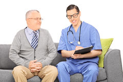 Male healthcare practitioner writing down notes and gentleman si Royalty Free Stock Images