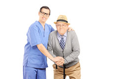 Male healthcare professional assisting an old man with cane Royalty Free Stock Photography
