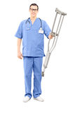 Male healthcare professional holding a pair of crutches Royalty Free Stock Images