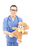 Male healthcare professional in uniform holding a teddy bear Royalty Free Stock Image