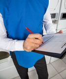 Male Helper Checking List In Laundry Royalty Free Stock Image