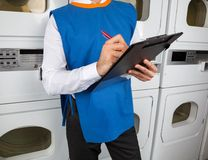 Male Helper Writing On Clipboard In Laundromat Stock Photography