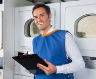 Male Helper Writing On Clipboard In Laundry Stock Photography