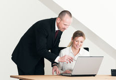 Male helping female colleguage. Male standing in suit and pointing pen at computer screen. Female sitting at desk looking at computer screen and smiling Royalty Free Stock Photos