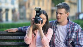 Male helping girlfriend to make photo with new professional camera, hobby. Stock footage stock video