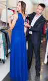 Male is helping his girl with trying on dark blue dress Stock Photos