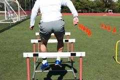 Male high school athlete bounding over hurdles Stock Photo