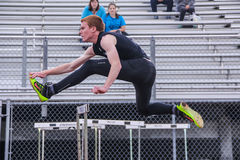 Male high school athlete clears the hurdle Stock Image