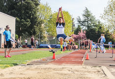 Male High school athlete at peak of long jump in track meet. Corvallis, Oregon, April 6, 2016: Male high school athlete competes in long jump event in early Stock Photos