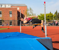 Male High school athlete tries to clear bar in high jump in track meet Royalty Free Stock Image