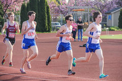 Male High school athletes cluster near beginning of 3000 meter race Stock Images