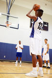 Male High School Basketball Player Shooting Penalty. With Coach Watching Royalty Free Stock Image