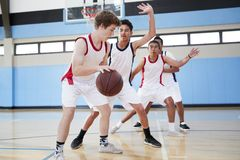 Male High School Basketball Team Dribbling Ball On Court stock photos