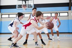 Male High School Basketball Team Dribbling Ball On Court royalty free stock images