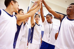 Male High School Basketball Team Having Team Talk With Coach. Looking Happy Royalty Free Stock Photography