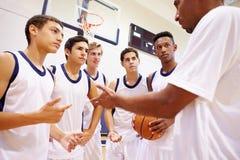 Male High School Basketball Team Having Team Talk With Coach. Male High School Basketball Team Having Motivated Team Talk With Coach In Gymnasium Royalty Free Stock Photos