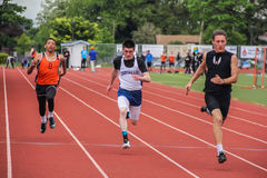 Male high school runners complete 100 meter race Royalty Free Stock Photo