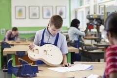 Male High School Student Building Guitar In Woodwork Lesson. Male High School Student Builds Guitar In Woodwork Lesson stock images