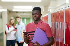 Portrait Of Male High School Student Bullied By Text Message In. Male High School Student Bullied By Text Message In Corridor Stock Images