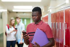Male High School Student Bullied By Text Message In. Unhappy Male High School Student Bullied By Text Message In Corridor Royalty Free Stock Photos