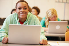 Male High School Student At Desk In Class Using Laptop Royalty Free Stock Image