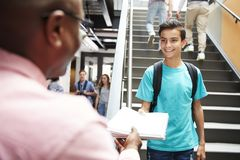 Male High School Student Handing Project To Teacher In Busy Corridor royalty free stock image
