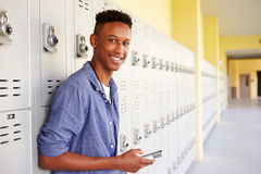 Male High School Student By Lockers Using Mobile Phone Stock Photo