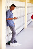 Male High School Student By Lockers Using Mobile Phone Stock Images