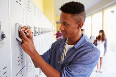 Male High School Student Opening Locker Stock Image