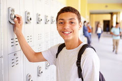 Male High School Student Opening Locker. Whilst Looking At Camera Smiling stock photos