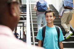 Male High School Student Talking With Teacher In Busy Corridor royalty free stock photography