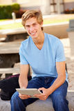 Male High School Student Using Digital Tablet Outdoors. Looking At Camera Smiling Stock Images