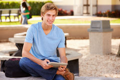 Male High School Student Using Digital Tablet Outdoors. Sitting Down Smiling Stock Images